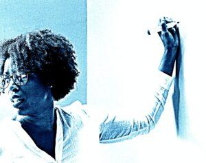 Frau hält Marker an Whiteboard und blickt entgegengesetzt in den Raum