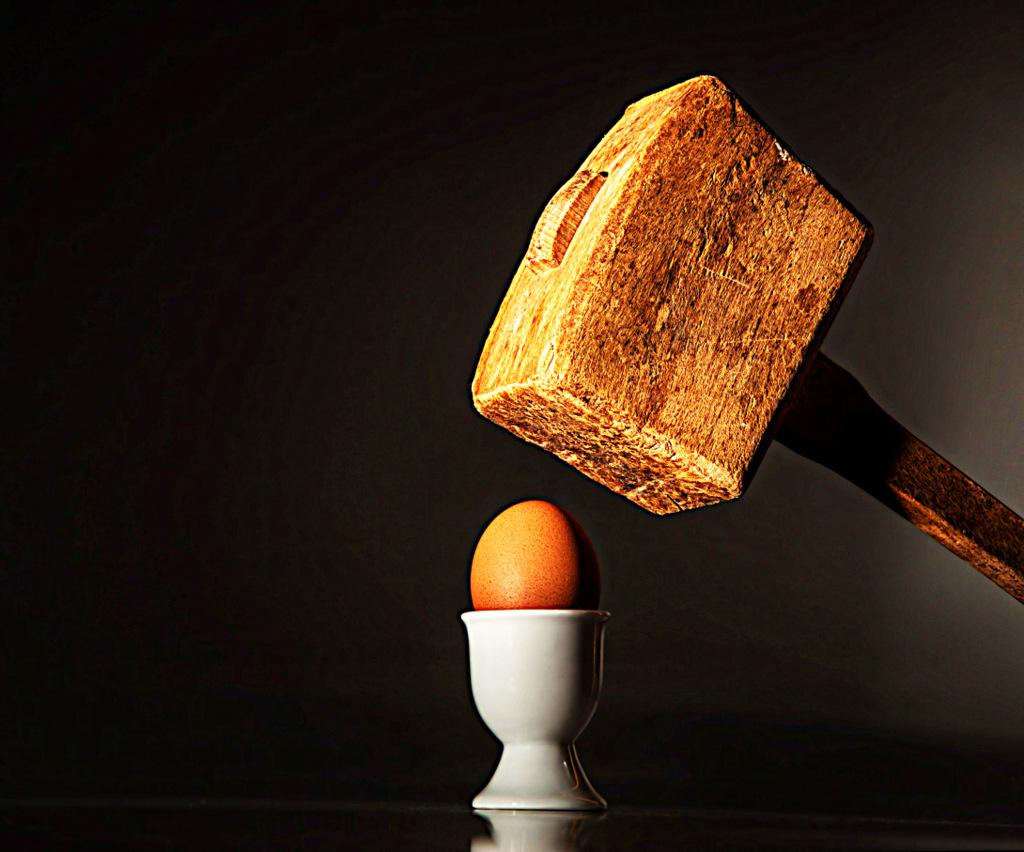 Holzhammer über einem Ei in einem Eierbecher