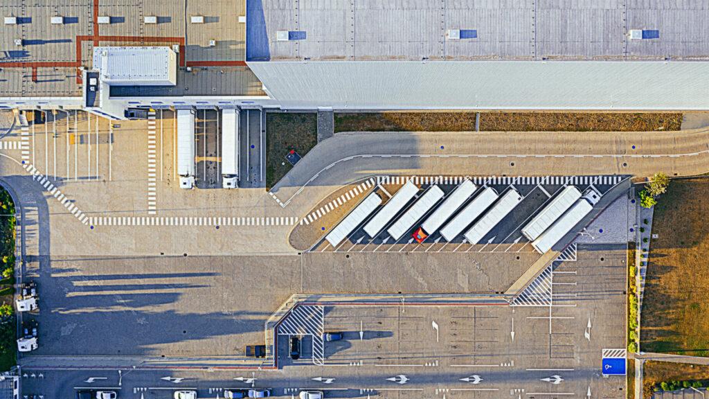 Luftbild: Firmengelände von oben mit Hallle, LKW und Parkplatz