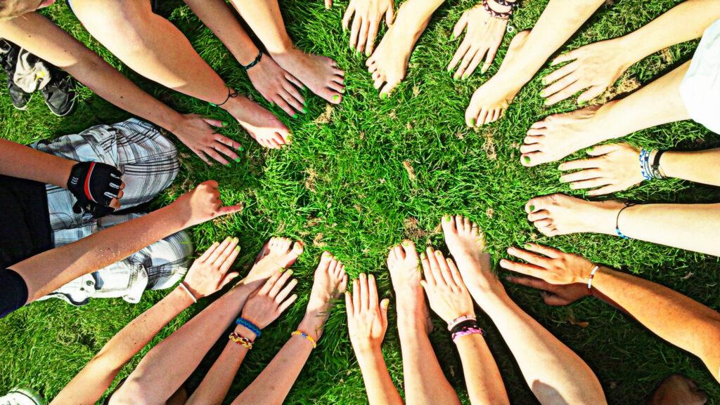Blick von oben auf Hände unterschiedlicher Menschen, auf Rasenfläche