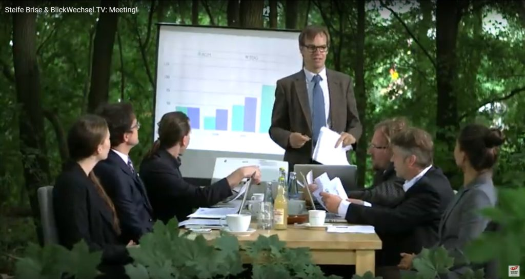 Eine Besprechungsszene im Wald: Ein Mann steht vor einer Leinwand, drei andere Menschen sitzen am Besprechungstisch und hören dem ersten zu.
